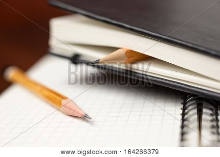Pencils on the pages of an closed notebook