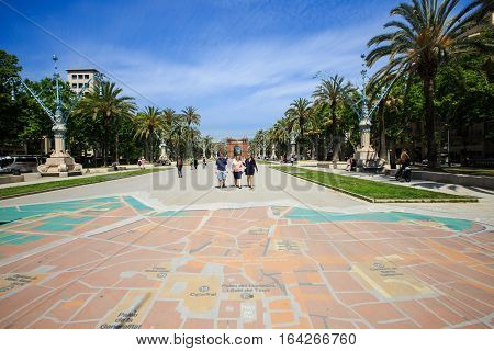 Barcelona, Spain - May 27, 2016: many tourists near the Arc de Triomphe in sunny summer day, city map on the ground