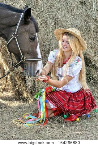 ukrainian teenage girl in traditional clothes feeds horse in the farm
