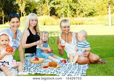 Three female friends with toddler children in the backyard
