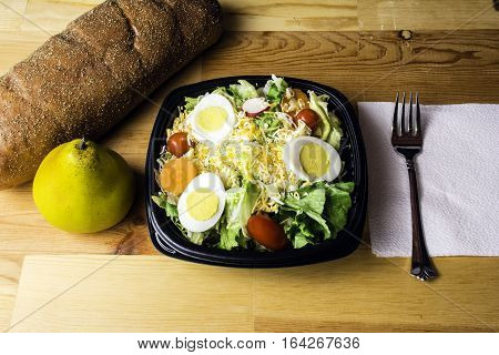 fresh garden salad of lettuce tomato radish carrot cheese and egg with pear and bread on wood background