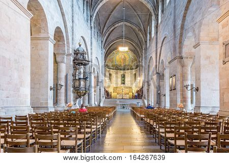 Lund, Sweden, May 23, 2016, Interior of Lund Cathedral, towards the apse and high altar. A few unknown persons are sitting in the huge basilica. The church was consecrated 1145.