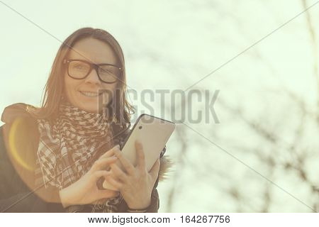 Portrait of a girl surfing the internet on a tablet outdoor, urban scene