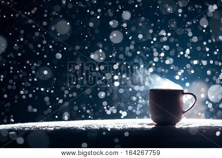 mug with warm tea in snow winter weather; backlighted cup of hot coffee on night snowy background;