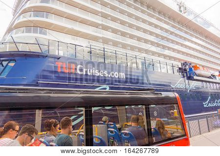 Copenhagen, Denmark, July 13, 2016, Unknown persons sitting in a tourist bus in Copenhagen harbour in front of a huge cruise Ship.