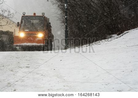 Orange snowplow drives to clean up the snowy road for heavy snowfall.