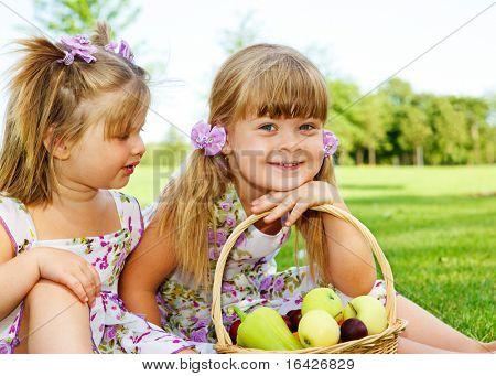 Dos niños dulces en jardín con cesta de fruta al lado