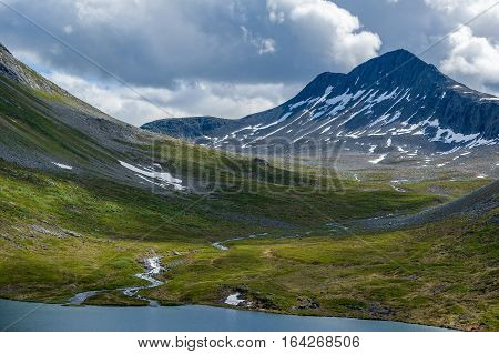 Mountain plateau with lake, fields and rocky mountain ahead. Scenic landscapes of Norwegian nature.