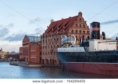 POLAND GDANSK - DECEMBER 18 2011: View of the ship-museum freighter Soldek near historic buildings of the island Olowianka. Gdansk is a Polish city on the Baltic coast and popular center of tourism.