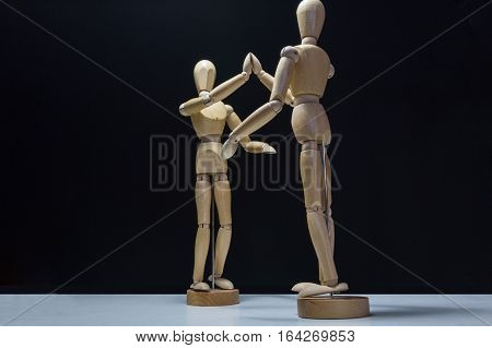 Wooden Mannequins-high 5 lower back - Two wooden mannequin's high fiving. Shot from behind the right mannequin.