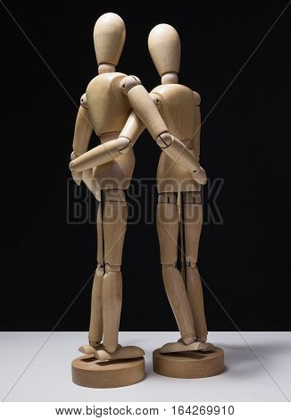 Wooden Mannequins-huggin from side 01 - Two wooden mannequins hugging and shot from behind and to the side with hands touching inappropriate places.