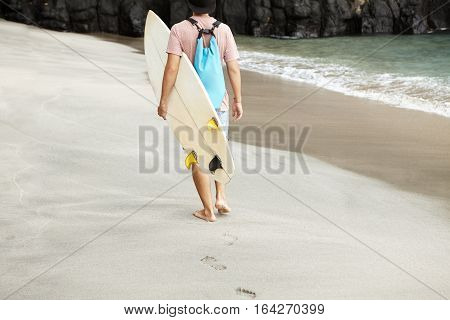 Sports, Hobby And Healthy Lifestyle Concept. Rear View Of Young Barefooted Man Walking Along Sea Sho