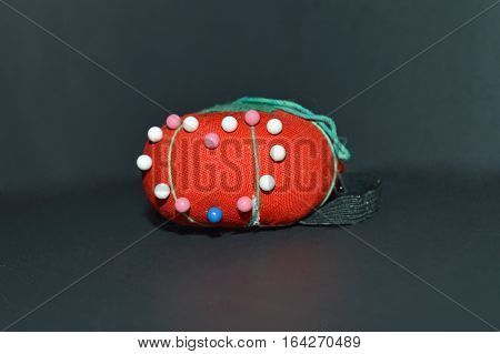Pin cushion with pins in heart shape on black background