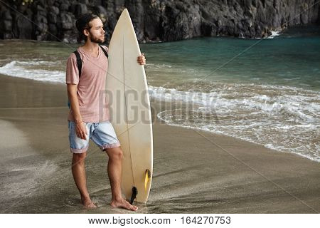 Young Handsome Male Model Posing With Surfboard On Exotic Beach For Travel Magazine, Against Beautif