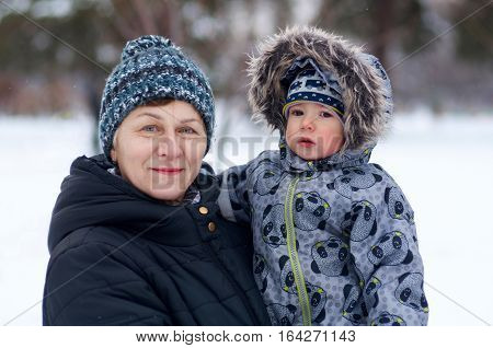 Happy grandmother hold in arms her little adorable grandchild in the winter park.Portrait of a happy family.
