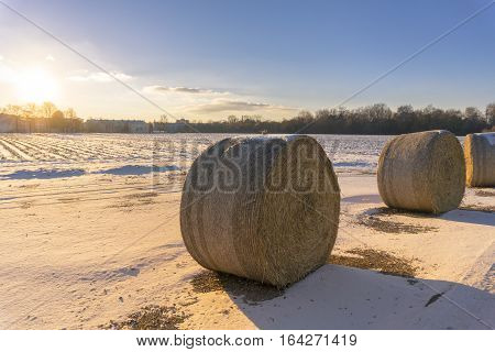 Hay Bales on a Field in front of a beautiful Winter Sunset
