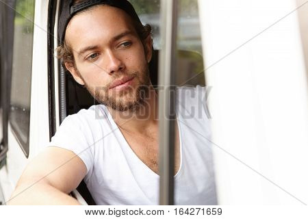 Bearded Student In Snapback Driving White Jeep, Sticking His Head And Elbow Out Of Open Window, Look