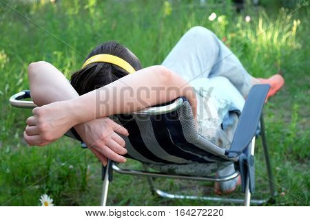 Woman lying down on folding deck chair on a meadow on vacation on a sunny summer day view from the back closeup. Focus on hands
