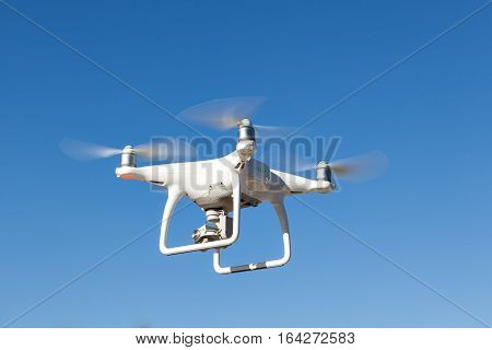 White copter hovers in the sky. Modern technology photo and video shooting.