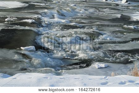 rapids on the river with rocks covered with ice and snow