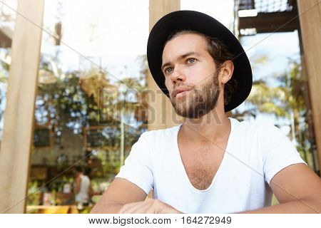 Close Up View Of Attractive Fashionable Young Bearded Businessman In V-neck Shirt And Black Hat Sitt