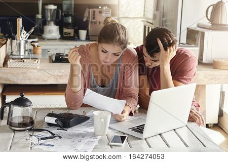 Young Couple Doing Paperwork In Kitchen: Frustrated Woman Reading Document Together With Her Husband
