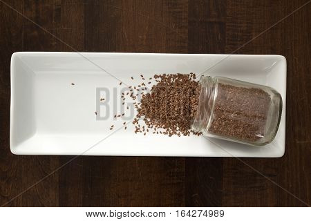 Flax Seeds Spilling Out Of Container, From Above