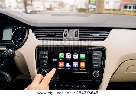 PARIS, FRANCE - DEC 2016: Man pressing home button on the Apple CarPlay main screen in modern car dashboard. CarPlay is an Apple standard that enables a car radio or head unit to be a display and controller for an iPhone. It is available on all iPhone 5 a