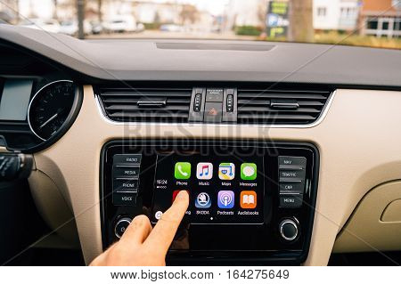 PARIS FRANCE - DEC 13 2016: Man pressing Now Playing button on the Apple CarPlay main screen in modern car dashboard. CarPlay is an Apple standard that enables a car radio or head unit to be a display and controller for an iPhone. It is available on all i
