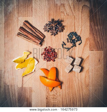 Various spices for mulled wine on old wooden table. Stars of anise, cinnamon sticks, cloves, brown sugar cubes, seasoning for cooking and baking, Christmas or New Year drink. Top view, copy space.
