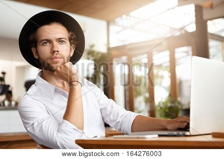 Indoor Shot Of Handsome Young Blogger In Headwear Working On New Post For His Blog Using Wi-fi On Ge