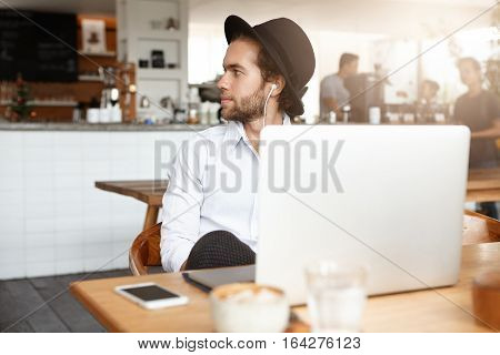 Young Bearded Hipster In Trendy Hat Listening To Music Or Audiobook On White Earphones, Sitting At W