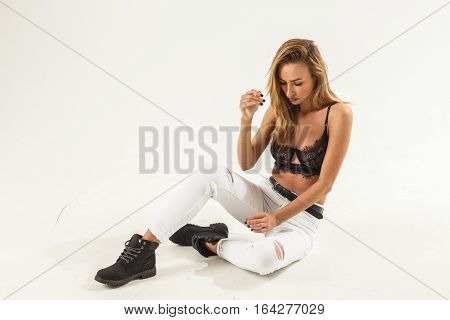 Beautiful sexy blonde girl in jeans and bra posing on white background