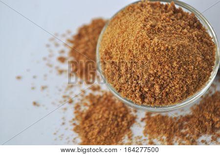 Organic coconut sugar - alternative sweetener in a glass bowl on white