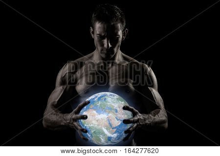 Very muscular naked man holding a glowing earth globe in his hands with rays of light - Elements of this image furnished by NASA