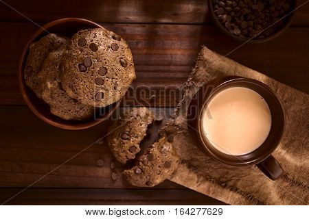 Homemade double chocolate chip cookies and a chocolate drink in a mug photographed overhead on dark wood with natural light (Selective Focus Focus on the top cookie in the bowl and on the chocolate drink)