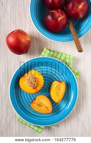 Fresh ripe nectarine fruit cut in pieces with other nectarines in bowl and on the side photographed overhead with natural light