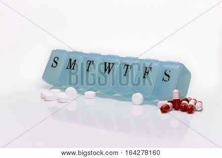 Pill box with multiple pills isolated on white.