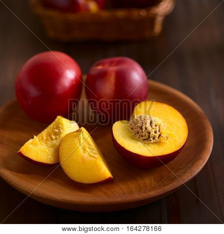 Fresh ripe nectarine fruits cut and whole on wooden plate photographed on dark wood with natural light (Selective Focus Focus on the front of the seed in the nectarine half)