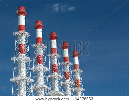 Five high industrial smoke pipes in-line over blue sky