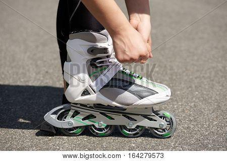 Woman is going roller skating. Putting on inline skates. Close up. Sport lifestyle.