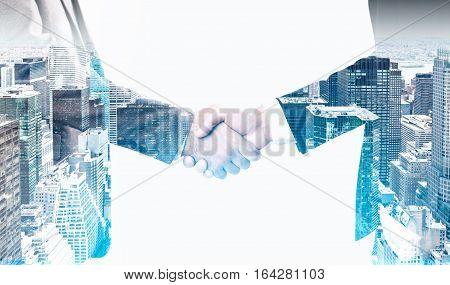 Close up of two men shaking hands and wearing suits. There is a large city panorama in the foreground. Concept of business meeting. Toned image. Double exposure