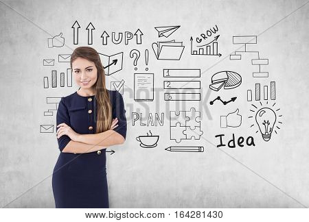 Portrait of a smiling businesswoman in a blue dress standing with her arms crossed near a concrete wall with business idea icons on it