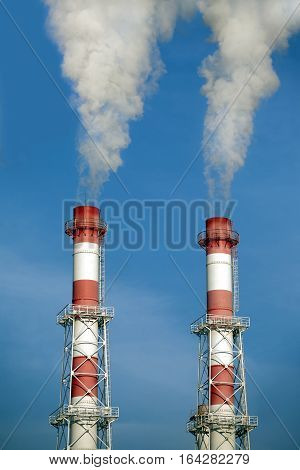 Two striped red and white industrial pipes with white smoke over cloudless blue sky. Front view closeup