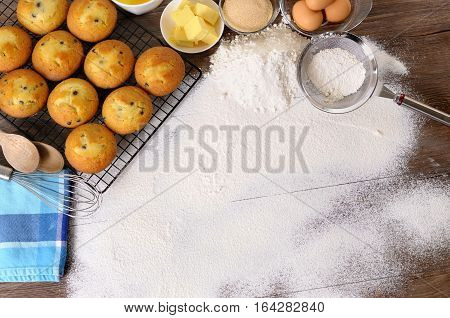Baking background with dusted flour on a dark wood table with freshly baked muffins and ingredients.