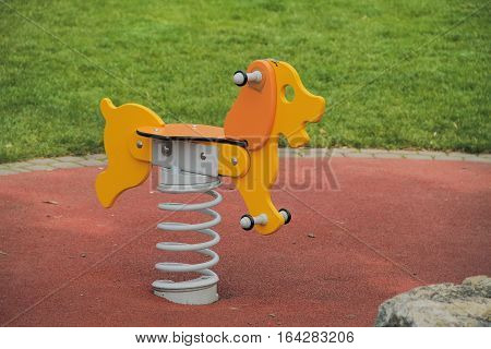 Interesting yellow wooden swing like. Dog on a spring