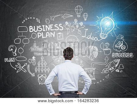 Rear view of a businessman standing with his hands on the waist and looking at a business plan sketch. A blue light bulb is shining in the corner.