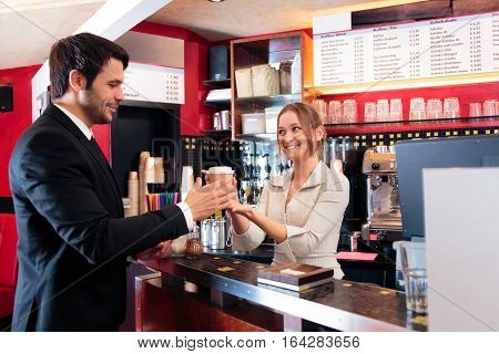 friendly bartender at a cafe, serving coffee-to-go to a customer