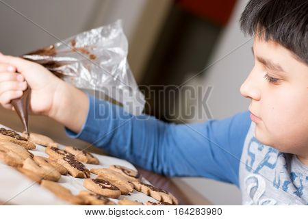 Kid Making Decoration On Gingerbread Cookie Close Up. Baking With Children
