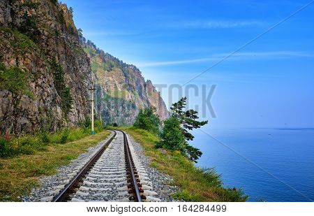 Single Track Railway Line On Edge Of Land Between Steep Rock And Lake Baikal